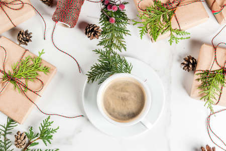 Coffee latte mug with Christmas gift or present box wrapped in kraft paper, decorated with christmas tree branches, pine cones, red berries, on white marble table, copy space Banque d'images
