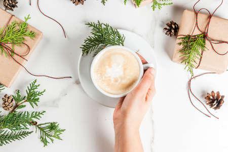 Vrouw handen met koffiemok, met kerstcadeau of huidige vak verpakt in kraftpapier, versierd met kerstboom takken, dennenappels, rode bessen, op wit marmeren tafel, kopie ruimte bovenaanzicht Stockfoto