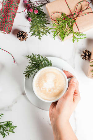 Woman hands holding coffee mug, with Christmas gift or present box wrapped in kraft paper, decorated with christmas tree branches, pine cones, red berries, on white marble table, copy space top view Stok Fotoğraf
