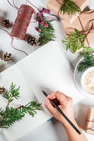 Woman write wishes or to do list in notebook, coffee mug, Christmas gift or present box, decorated with christmas tree branches, pine cones, red berries, on white marble table, copy space top view