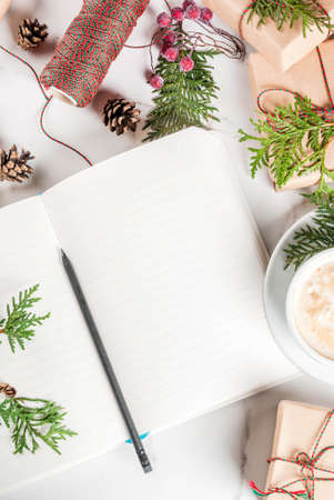 Blank notebook and pencil for wishes, to do list, coffee mug, Christmas gift or present box, decorated with christmas tree branches, pine cones, red berries, on white marble table, copy space top view