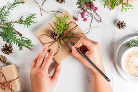 Woman write wishes on Christmas gift or present box, decorated with christmas tree branches, pine cones, red berries, on white marble table, or to do list in notebook, with coffee mug, copy space top view