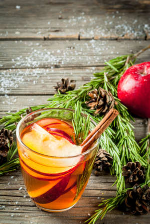Christmas, Thanksgiving drinks. Autumn, winter cocktail grog, hot sangria, mulled wine - apple, rosemary, cinnamon, anise. On old rustic wooden table. With cones, rosemary. Copy space