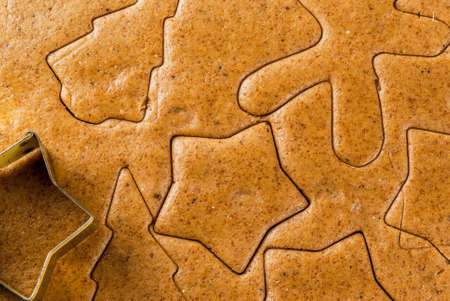 Christmas baking. Ginger dough for gingerbread, gingerbread men, stars, Christmas trees, close view, background, copy space top view