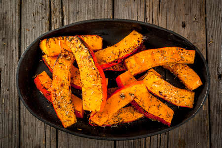 Traditional autumn dishes from pumpkin. Fried baked on grill pumpkin with spices, olive oil, herbs. On a baking sheet, on a rustic wooden old table. Top view copy space