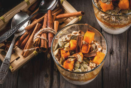 Traditional autumn dishes, spicy pumpkin pie overnight oatmeal with cinnamon, anise and maple syrup. In portioned glasses, on wooden old rustic table. Copy space top view