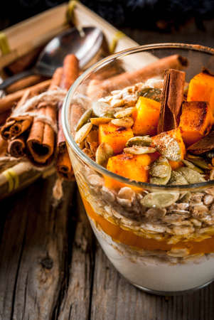 Traditional autumn dishes, spicy pumpkin pie overnight oatmeal with cinnamon, anise and maple syrup. In portioned glasses, on wooden old rustic table. Copy space