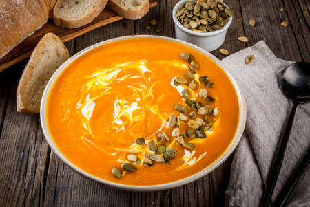 Traditional fall and winter dishes, hot and spicy pumpkin  soup with pumpkin seeds, cream and freshly baked baguette, on old rustic wooden table, copy space