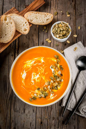 Traditional fall and winter dishes, hot and spicy pumpkin  soup with pumpkin seeds, cream and freshly baked baguette, on old rustic wooden table, copy space top view
