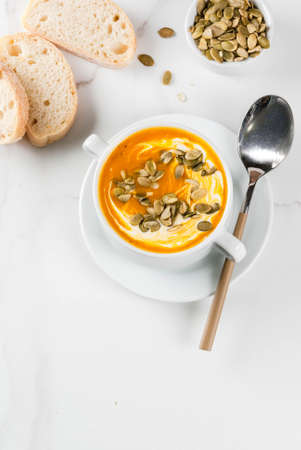 Traditional fall and winter dishes, hot and spicy pumpkin  soup with pumpkin seeds, cream and freshly baked baguette, on white marble table, copy space top view Stok Fotoğraf