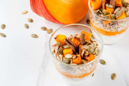 Traditional autumn dishes, spicy pumpkin pie overnight oatmeal with cinnamon, anise and maple syrup. In portioned glasses, on white marble table. Copy space