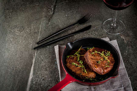 Lunch for one person. Homemade grilled beef steaks with thyme in a portioned frying pan, with a fork, knife and a glass of wine.  On black stone table, copy space top view