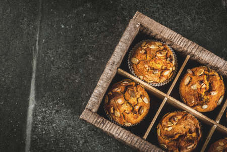 Autumn and winter baked pastries. Healthy pumpkin muffins with traditional fall spices, pumpkin seeds. In old wooden box, Black stone table, copy space top view