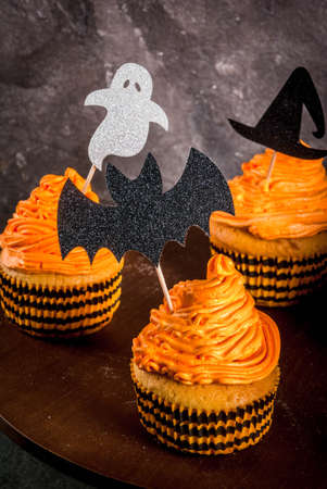 Simple idea of funny kids treat for Halloween: pumpkin cakes with cream, with decorations in the form of holiday symbols - ghost, witch, bat. On a black background, copy space