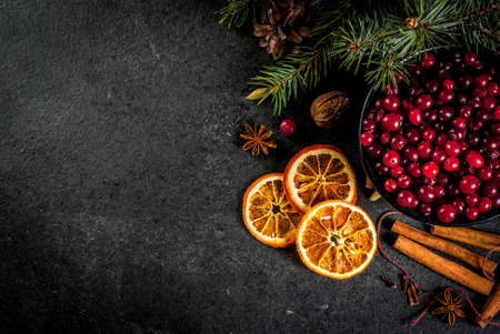 Ingredients for Christmas, winter baking cookies. Gingerbread, fruitcake, seasonal drinks. Cranberries, dried oranges, cinnamon, spices on a black stone table, copy space top view