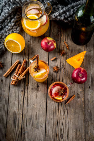 Traditional fall and winter drinks and cocktails. White and red autumn hot spicy sangria with anise, cinnamon, apple, orange, wine. In glass mugs, old rustic wooden table. Top view copy space Stock Photo