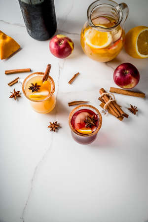 Traditional fall and winter drinks and cocktails. White and red autumn hot spicy sangria with anise, cinnamon, apple, orange, wine. In glass mugs, white marble table. Top view