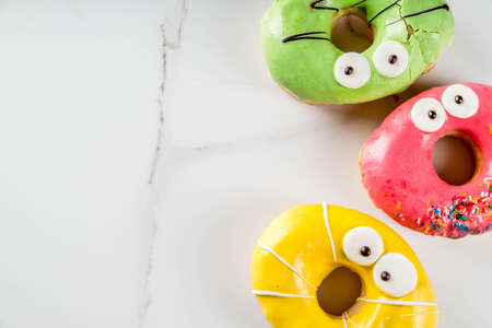 Ideas for children treats on Halloween. Colorful  donuts in the form of monsters with eyes, green, yellow, red chocolate sugar icing. On a white marble table. Copy space top view