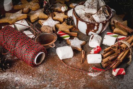 New Year, Christmas treats, sweets. Cup of hot chocolate with fried marshmallow, ginger star cookies, gingerbread men, striped candy, spices cinnamon anise, cocoa, powdered sugar.  Copy space Stok Fotoğraf