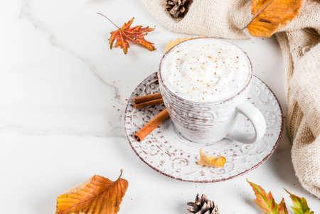 Herbst heiße Getränke. Kürbis-Latte mit Schlagsahne, Zimt und Anis auf weißem Marmortisch, mit Pullover (Decke), Blätter im Herbst und Tannenzapfen. Platz kopieren