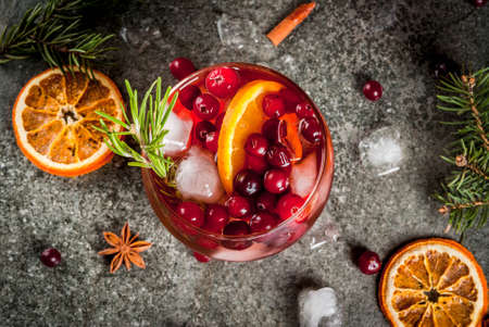 Christmas winter drinks. Cold cocktail with cranberries, orange, rosemary, with spices (cinnamon, anise) and ice, on a dark stone table, Copy space top view Stok Fotoğraf