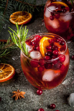 Christmas winter drinks. Cold cocktail with cranberries, orange, rosemary, with spices (cinnamon, anise) and ice, on a dark stone table, Copy space