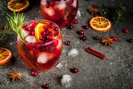 クリスマス冬の飲み物。カクテル クランベリー、オレンジ、ローズマリー、スパイス (シナモン、アニス) と暗い石のテーブル、コピー領域の氷冷
