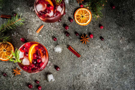 Christmas winter drinks. Cold cocktail with cranberries, orange, rosemary, with spices (cinnamon, anise) and ice, on a dark stone table, Copy space  TOP VIEW