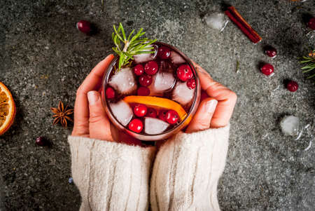 Christmas winter drinks. Girl drinks cold cocktail with cranberries, orange, rosemary, with spices (cinnamon, anise) and ice, on a dark stone table, Copy space top view, hands