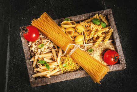 Selection of various raw italian pasta with basil leaves and cherry tomato, in old wooden box on dark stone table, top view copy space