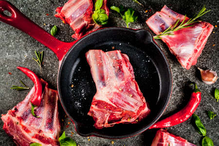 Raw fresh meat, uncooked lamb or beef ribs with hot pepper, garlic and spices with frying pan skillet on dark stone background, copy space top view Reklamní fotografie