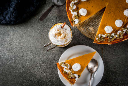 Traditional autumn dishes. Halloween, Thanksgiving. Spicy pumpkin pie with whipped cream & pumpkin seeds, pumpkin latte with cinnamon on black stone table with blanket. Copy space top view Stock Photo