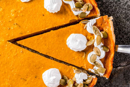 Traditional autumn dishes. Halloween, Thanksgiving. Sliced spicy pumpkin pie with whipped cream & pumpkin seeds on black stone table. Top view copy space