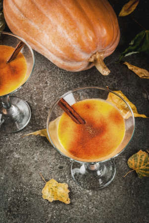 Fall and winter drinks. Thanksgiving and Halloween cocktails. Pumpkin pie margarita with cinnamon stick, on black stone table. Cozy home, with autumn leaves, plaid, pumpkin, copy space top view