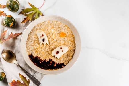 Halloween food recipes for children, Kids breakfast with sweet pumpkin oatmeal  with scary edible banana ghosts and chocolate sauce, on white background, top view copy space