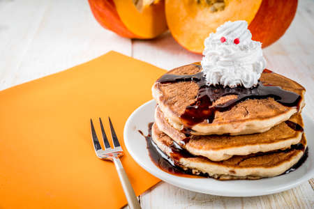 Ideas for childrens breakfast, treats for Thanksgiving and Halloween. Pancakes with chocolate sauce and whipped cream in the form of a ghost. On a white wooden table, copy space