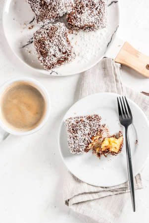 Australian food. Traditional dessert Lamington - pieces of biscuit in dark chocolate, sprinkled with coconut powder chips. On a marble plate, white table. With coffee mug. Copy space top view