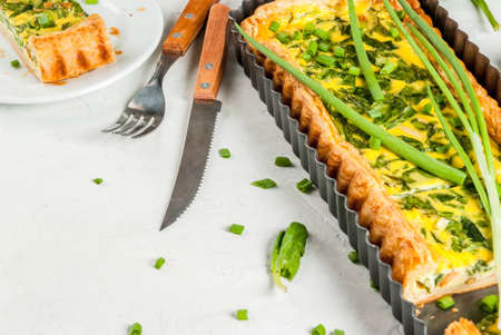 French home cooking. Casserole. Pie. quiche lorraine from puff pastry, with young green onions and spinach. On white concrete table. Cut. In form for baking. Plate, fork, knife. Copy space