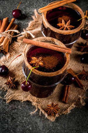 Autumn and winter drinks. Hot cherry sangria with cinnamon, anise, wine and spices. On a stone dark and wooden background with ingredients, Copy space