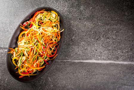 Veganistisch eten, dieet. Plantaardige noedels, pasta van wortel, courgette, paprika. Klaar om te bakken op een stenen tafel. Ruimte bovenaanzicht kopiëren Stockfoto - 87614851