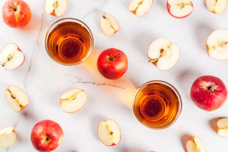 Fresh organic farm apple juice in glasses with raw whole and sliced red apples, on white marble table, copy space top view