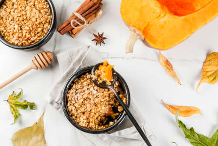 Dietary autumn pastries, breakfast. Crumble pumpkin pie, maple syrup and oatmeal flakes, in plate saucers, on a white marble table. Copy space Stock Photo - 87781385