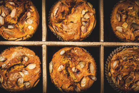 Autumn and winter baked pastries. Healthy pumpkin muffins with traditional fall spices, pumpkin seeds. In old wooden box, Black stone table, close top view
