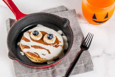 Funny food for Halloween. Kids breakfast pancake decorated like mummy with white chocolate sauce, banana, berries, with pumpkin smoothie juice, white table copy space