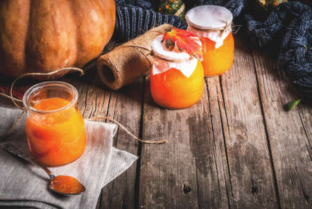 Autumn recipes, dishes from a pumpkin. Sweet spicy pumpkin jam in a serving jar, with a spoon, on an old rustic wooden table decorated with pumpkins, autumn leaves, a blanket. Copy space