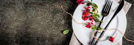 Herfst voedsel achtergrond concept. Thanksgiving-diner, Donkere stenen tafel met bestekmes, vork met herfstbessen als decoratie. Zwarte achtergrond. Ruimte boven banner kopiëren Stockfoto