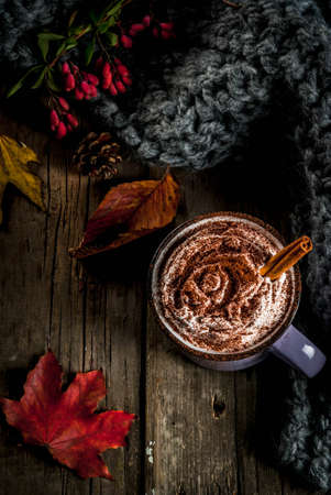Autumn drinks, hot chocolate or cocoa with whipped cream and spices (cinnamon, anise), on the old rustic wooden table, with a warm cozy blanket, hay berry and leaves copy space top view