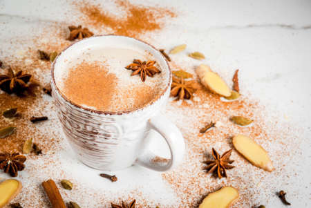 Traditional indian masala chai tea with spices - cinnamon, cardamom, anise, white background. Copy space Imagens