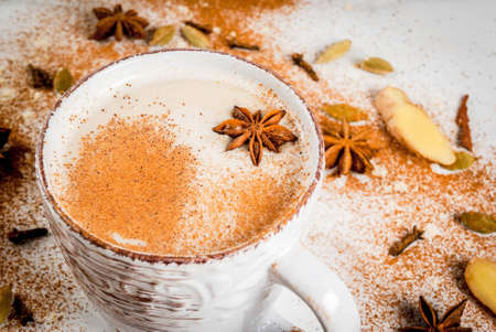 Traditional indian masala chai tea with spices - cinnamon, cardamom, anise, white background. Copy space Stockfoto