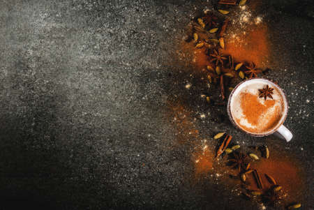 Traditional indian masala chai tea with spices - cinnamon, cardamom, anise, dark stone background. Copy space top view